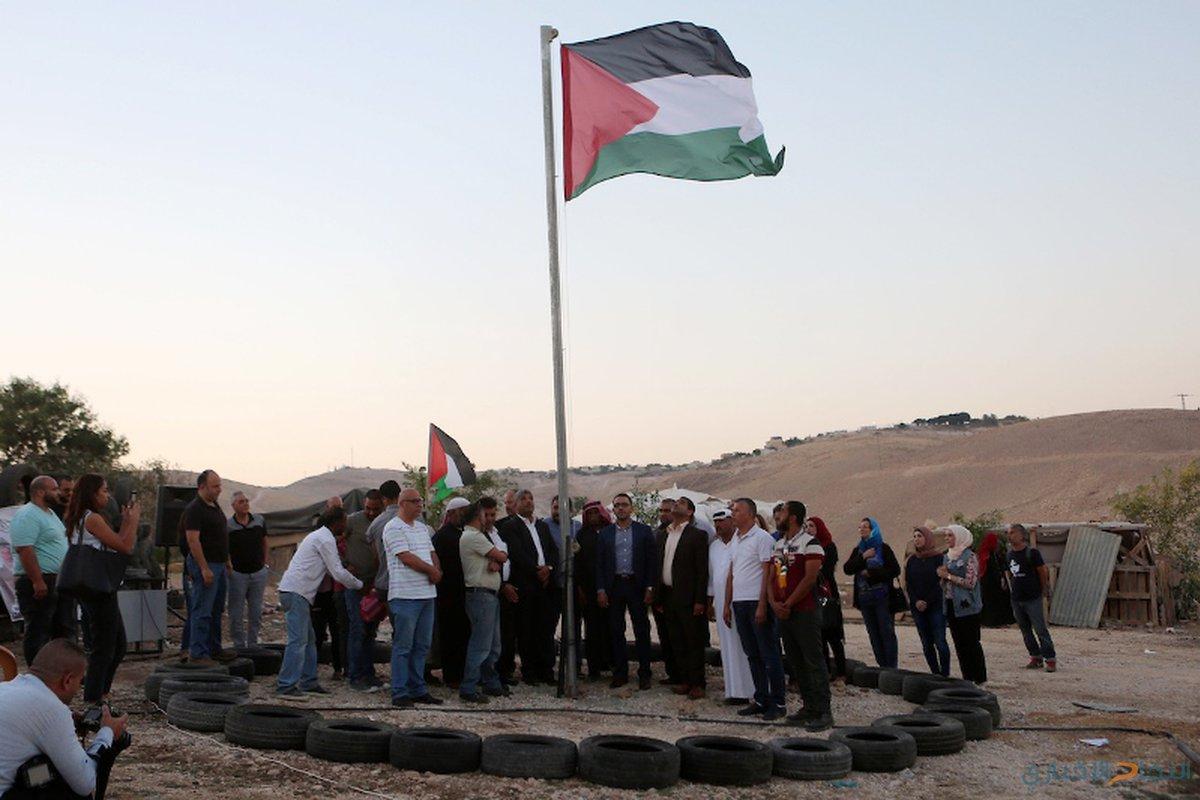 متظاهرون فلسطينيون يتجمعون حول العلم الفلسطيني في قرية خان الأحمر البدوية في الضفة الغربية المحتلة ضد خطة إسرائيل لهدم القرية في 26 سبتمبر 2018.
