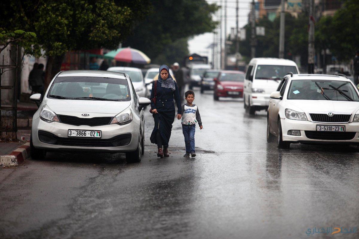 مواطنون  يسيرون في الشوارع المبتلة خلال يوم ممطر في مدينة غزة