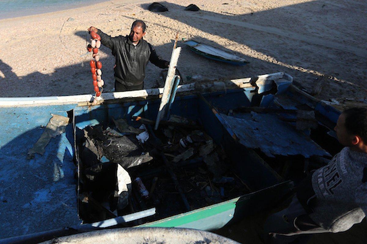 صيادون فلسطينيون يتفقدون قاربهم المستهدف بغارة جوية إسرائيلية على شاطئ دير البلح وسط قطاع غزة في 10 مارس / آذار 2019.