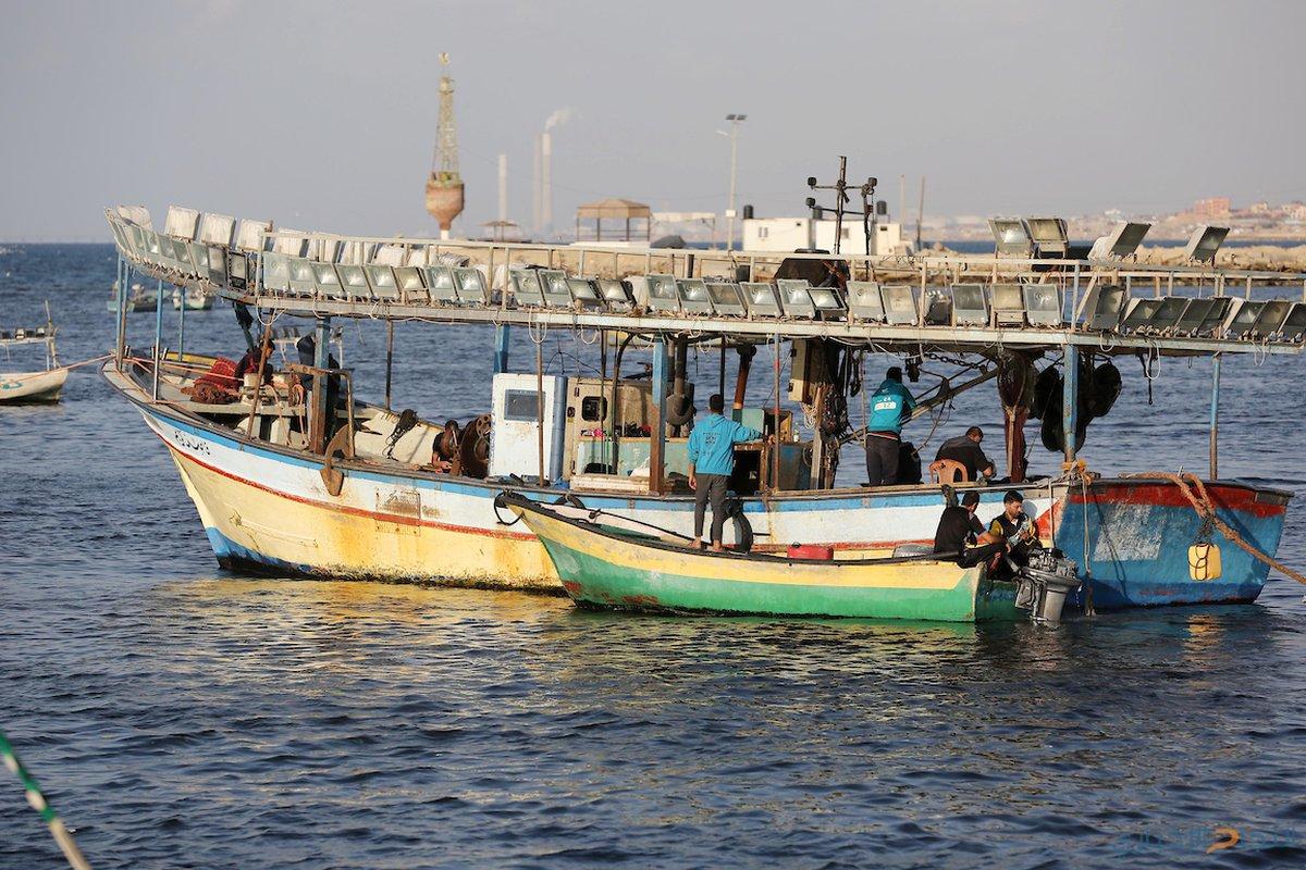 صيادون فلسطينيون يعملون على قوارب الصيد الخاصة بهم في البحر في الميناء البحري في مدينة غزة.